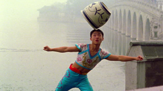 MS Asian man balancing + spinning large pot on head with Seventeen Arch bridge in background / Beijing, China