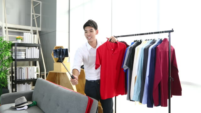 asian man  blogger broadcasting a video for selling product online such as  hats, shoes, headphones, clothing, safety headers.shopping online concept - selling stock videos & royalty-free footage