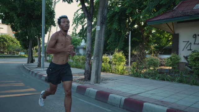 asian man body muscle speed running on bangkok road. ​ - attitude stock videos & royalty-free footage