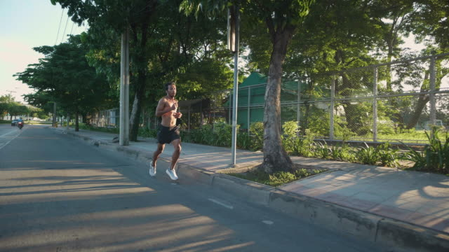 asian man body muscle speed running on bangkok road.  - young men stock videos & royalty-free footage