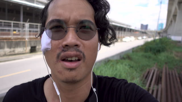 vidéos et rushes de homme asiatique bras cassé parlant sur la caméra, vlog, bangkok thaïlande. - photophone