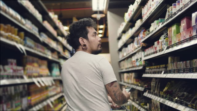asian man buying food in supermarket. - mercanzia video stock e b–roll