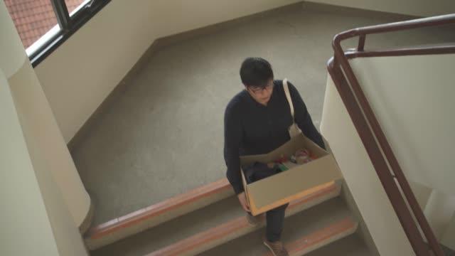 vídeos de stock, filmes e b-roll de homem asiático carregar suas coisas em uma caixa descendo escadas, deixando seu emprego - embalagem cartonada