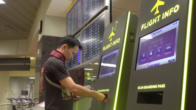 Asiatischer Mann überprüfen Fluginformationen mit Maschine im Flughafen-terminal
