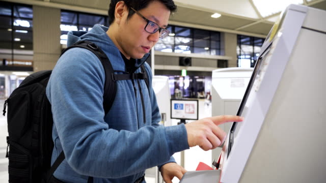 asian man check-in at the airport with self-service machine - examining stock videos & royalty-free footage