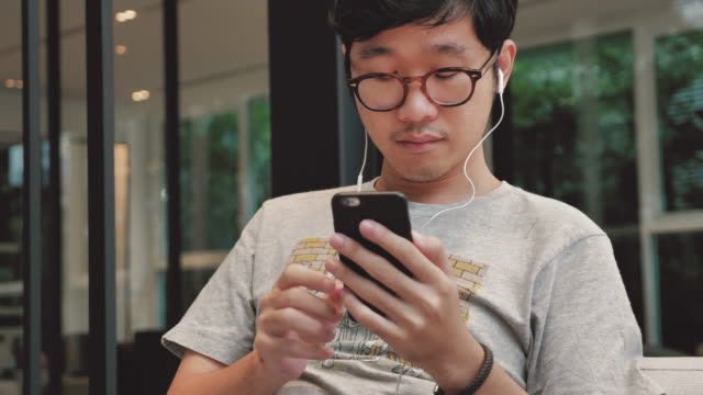 Asian man choosing and listening music on smart phone, 4K