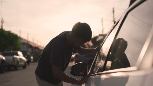 asian man cleaning  car in home at sunset - polishing stock videos & royalty-free footage