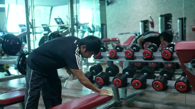 asian man cleaning exercise equipment in fitness - cleaning equipment stock videos & royalty-free footage