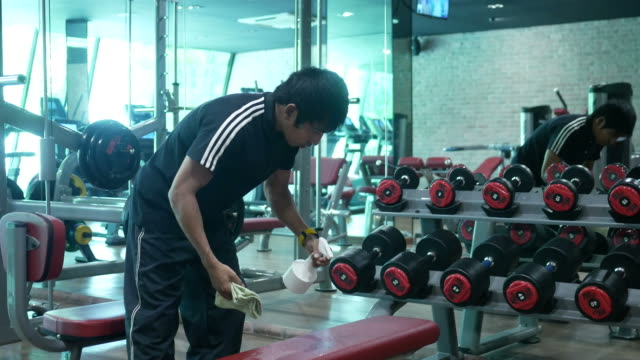 asian man cleaning exercise equipment in fitness - exercise equipment stock videos & royalty-free footage