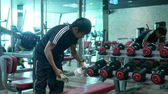 vídeos de stock, filmes e b-roll de homem asiático, limpeza de equipamentos de ginástica em fitness - equipamento para exercícios