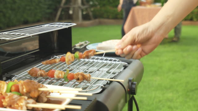 asian man cooking barbecue grill and sausage for a group of friends to eat party in garden at home. group of friends having outdoor garden barbecue laughing with alcoholic beer drinks - formal garden party stock videos & royalty-free footage