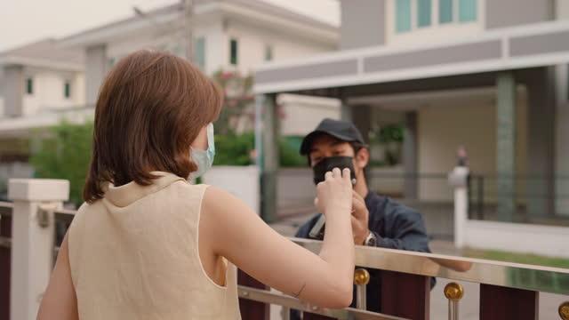 vídeos de stock, filmes e b-roll de homem asiático entregando mantimentos para clientes de mulheres asiáticas - receber