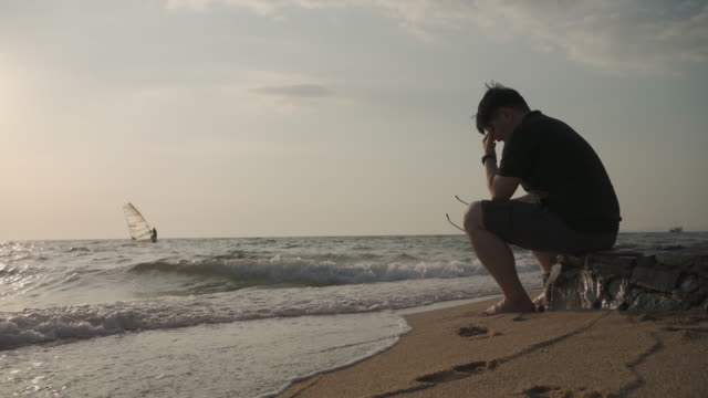 asian man depressing and sitting alone by the beach - one mid adult man only stock videos & royalty-free footage