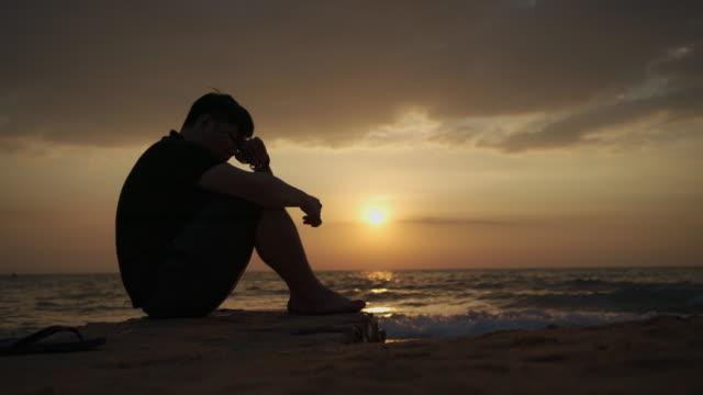 stockvideo's en b-roll-footage met aziatische mens die en door het strand bij zonsondergang, pattaya deprimeert en zit - overstuur