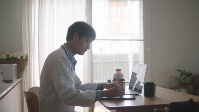 stockvideo's en b-roll-footage met aziatische mensarts die telemedicine uitvoert die aan een patiënt thuis luistert. - laboratoriumjas