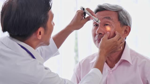 アジア人男性医師は、患者の目を病院の上級検査官、上級アジア人男性に診てもらい、医療従事者による健康診断を受ける。 - 年次イベント点の映像素材/bロール