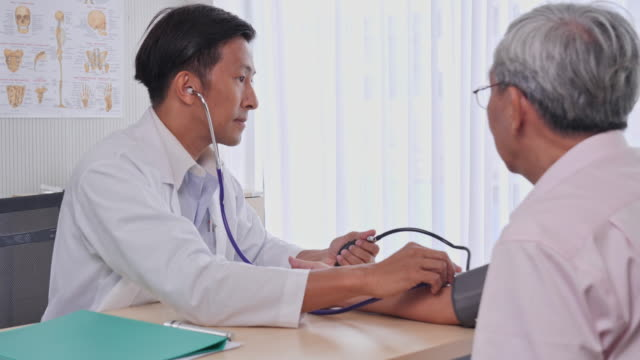 asian man doctors measure blood pressure to a senior patient in the examination room of the hospital, senior asian man to get a health check by medical professionals. - medical examination room stock videos & royalty-free footage