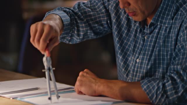 Aziatisch mens tekenen met kompassen achter zijn Bureau