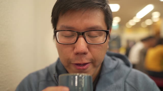 slo mo asian man drinking japanese hot tea in restaurant - loneliness stock videos & royalty-free footage