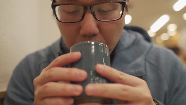 slo mo asian man drinking japanese hot tea in restaurant - front view stock videos & royalty-free footage