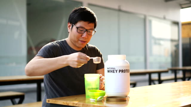 Asian man drinking whey protein drink after gym