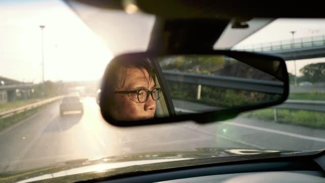 asian man drives a car at sunset reflection face. - car interior stock videos & royalty-free footage