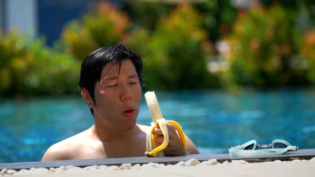 slo mo - asian man eating banana after swim - peel stock videos & royalty-free footage