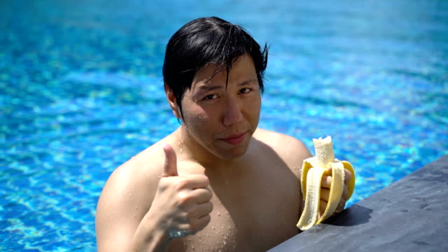 asian man eating banana in swimming pool before thumbs up - thumbs up stock videos & royalty-free footage