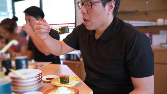 asian man eating capelin masago nigiri, japanese food - nigiri stock videos and b-roll footage