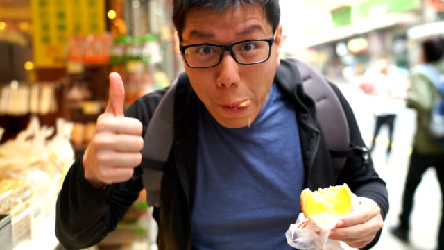 asian man eating egg tart in street food in hong kong - bakery stock videos and b-roll footage