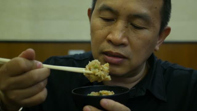 vídeos de stock, filmes e b-roll de comida asiática homem comendo - comida japonesa