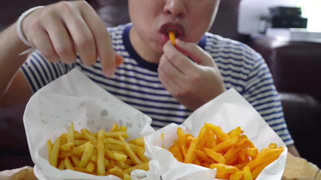 asian man eating french fries. - chips stock videos & royalty-free footage