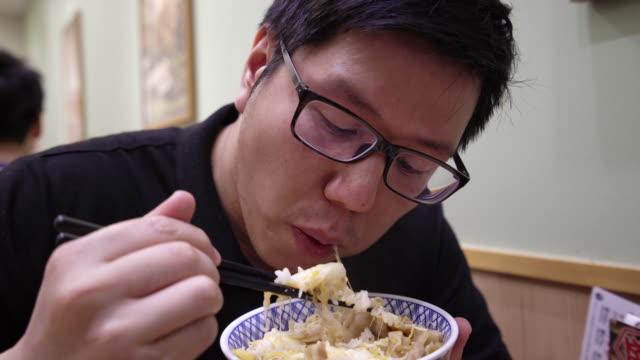レストランで牛丼を食べるアジア人男性。 - fast food点の映像素材/bロール