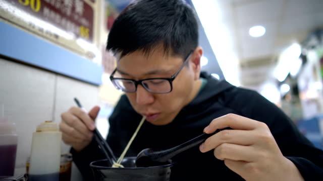 vídeos de stock, filmes e b-roll de asian homem comendo macarrão de hong kong na sopa no restaurante - bolinho de massa