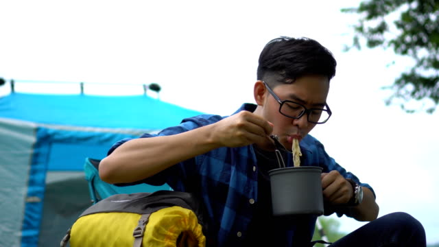 Asian Man eating instant noodle in countryside-camping area
