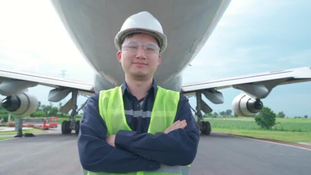 asiatische mann ingenieur wartungsflugzeug hält weißen helm vor dem flugzeug von reparaturen, reparaturen, modernisierung und renovierung in flughafen. - qualitätsprüfer stock-videos und b-roll-filmmaterial