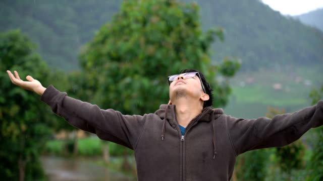 asian man enjoy the rain - surrendering stock videos & royalty-free footage