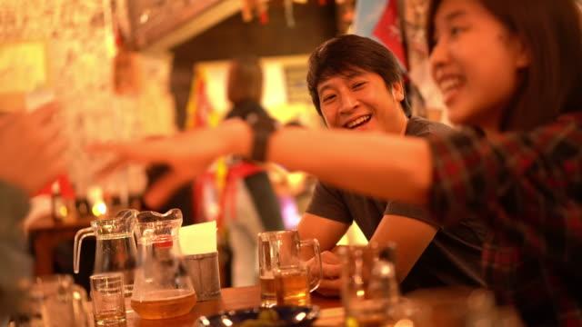居酒屋パブで飲んで友達のジョークを聞いているアジア人男性 - 居酒屋点の映像素材/bロール