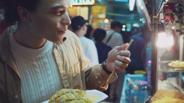 vídeos de stock e filmes b-roll de asian man enjoying food truck life in khao san road. bangkok, - pauzinhos
