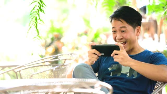 アジア男を楽しんで彼自身間のゲーム彼の携帯電話に - ゲーム点の映像素材/bロール