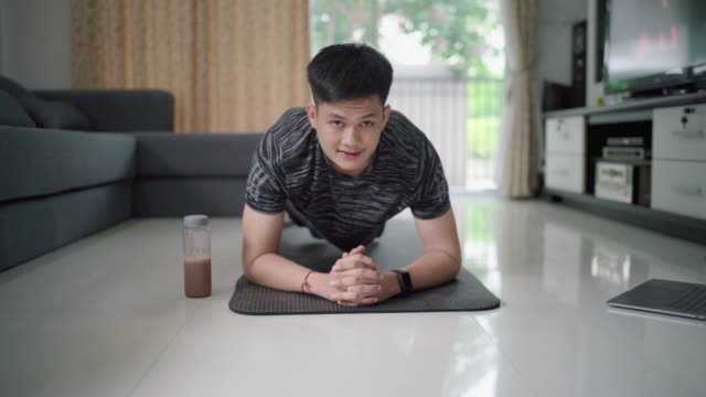 asian man exercise at home with the help of online tutorials in living room. - exercise room stock videos & royalty-free footage