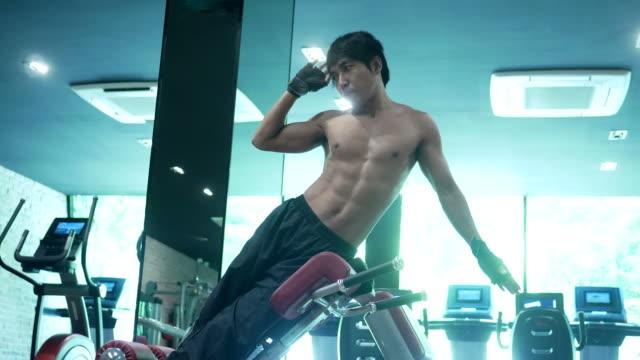 vídeos de stock, filmes e b-roll de homem asiático exercitar no fitness - aparelho de musculação