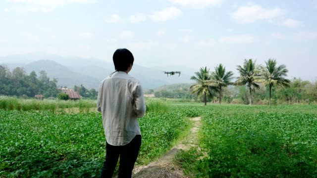asian man farmer pilot using drone remote controller - communications tower stock videos & royalty-free footage