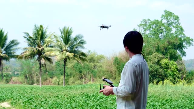 vídeos de stock e filmes b-roll de asian man farmer pilot using drone remote controller - pairar