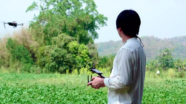 asian man farmer pilot using drone remote controller - drone pilot stock videos and b-roll footage