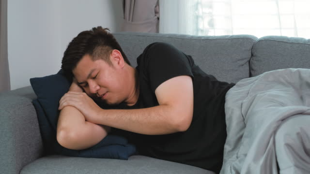 asian man flu and cold he coughs and sneezes sleeping on bed at home . feeling sick concept. - bedclothes stock videos & royalty-free footage