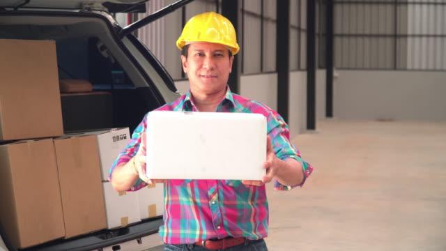 vídeos y material grabado en eventos de stock de el hombre asiático capataz entregando paquete a usted en el almacén - piso de edificio