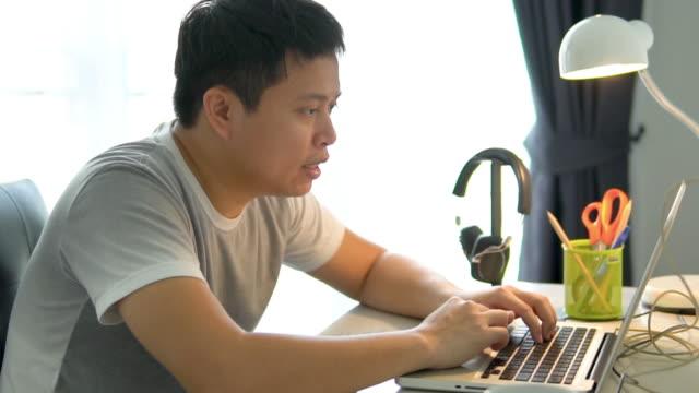 vídeos de stock, filmes e b-roll de homem asiático freelance trabalhando em casa. - searching