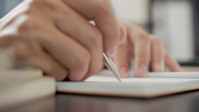 asian man freelance writer is writing on a notebook. - list stock videos & royalty-free footage
