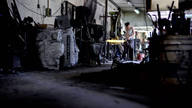 アジア男ワーク ショップ鍛冶屋で鉄を研削 - 金属点の映像素材/bロール